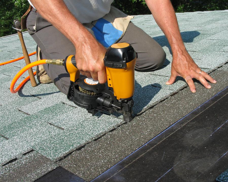 man putting asphalt roof tiles